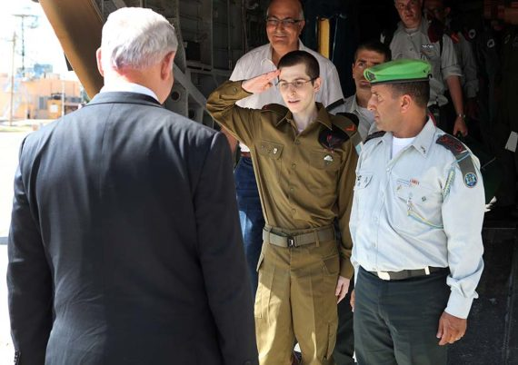 Israeli soldier Gilad Shalit salutes Israeli Prime Minister Benjamin Netanyahu on arrival at Tel Nof air force base
