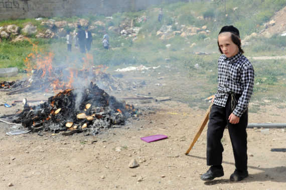 An Ultra-Orthodox Jewish boy walks by a fire burning leavened products before the start of the Jewish holiday Passover in Jerusalem