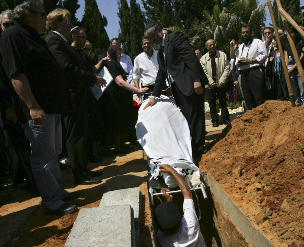 RAANANA, ISRAEL - APRIL 20: The shroud-covered body of Virginia Tech Professor of Engineering Liviu Librescu is lowered into his grave during his funeral on April 20, 2007 in the municipal cemetery in Raanana, Israel. Librescu, an internationally respected aeronautics engineer and a lecturer at Virginia Tech for 20 years, was a Holocaust survivor who later escaped to Israel from Communist Romania. Librescu has been hailed as a hero for saving the lives of several students by blocking shooter Cho Seung-Hui before he was gunned down in the attack which left 32 students and faculty members dead on the Virginia Tech campus on April 16, 2007 in Blacksburg, Virginia, USA. (Photo by David Silverman/Getty Images)