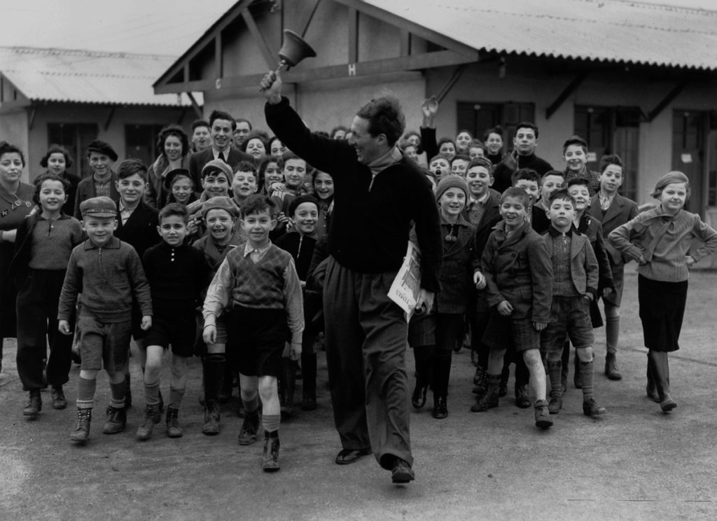 11th January 1939: A camp leader ringing the dinner bell at a camp for young Jewish 'Kindertransport', refugees from Germany and Austria, at Dovercourt Bay near Harwich. (Photo by Reg Speller/Fox Photos/Getty Images)